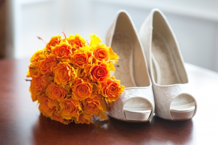 wedding shoes and bouquet of orange roses nobody
