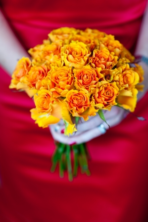 woman in a red dress holding a bouquet of orange roses photo