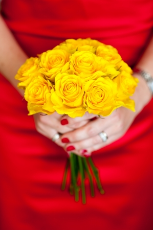 woman in a red dress holding a yellow bouquet of roses photo