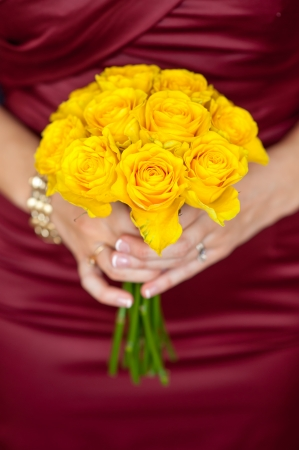 woman in a red dress holding a yellow bouquet of flowers photo