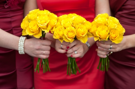 three bridesmaids holding wedding bouquets of yellow roses photo