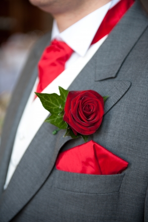 buttonhole: groom wearing red rose buttonhole at wedding