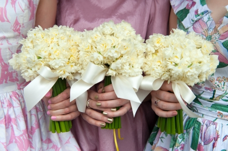 bridesmaids: three daffodil wedding bouquets held by bridesmaids in vintage dresses Stock Photo