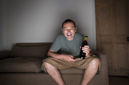 comedy: man drinking beer and laughing at the tv Stock Photo