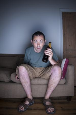 man watching tv: man watching tv in disbelief