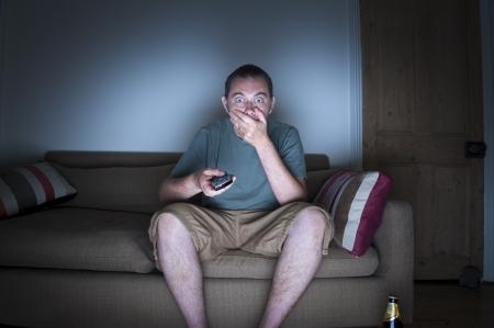 cara sorprendida: el hombre que cubre la boca viendo la televisión Foto de archivo