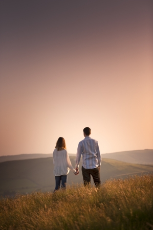lovers holding hands: couple watching the sunset
