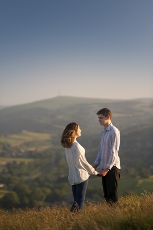 romantic young couple holding hands on a hillside photo