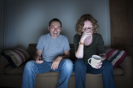 hilarity: couple watching television laughing and embarrassed