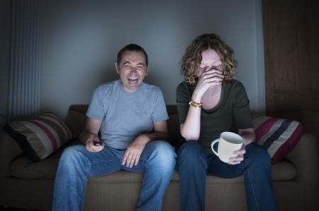 Paar vor dem Fernseher lachen und peinlich