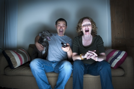 middle aged couple and dog laughing at the television