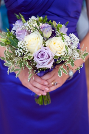 purple rose: bridesmaid holding a wedding bouquet of white and purple roses Stock Photo