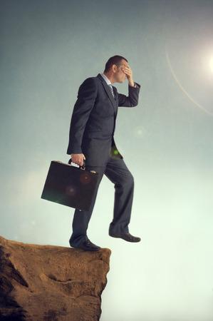 over the edge: businessman with hands over eyes steps off a cliff Stock Photo