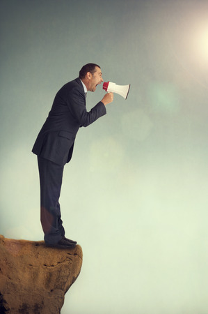 amplified: businessman with loudhailer on the edge of a cliff shouting