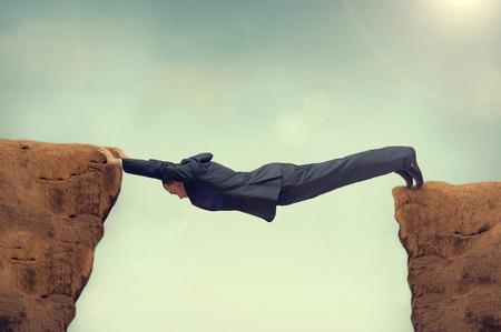 Geschäftsmann zwischen einem Felsen und einem harten Platz