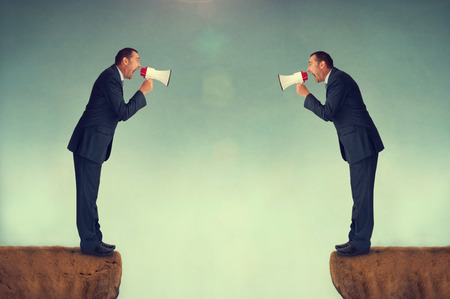 verbal communication: businessman shouting at each other through loudhailers or megaphones Stock Photo