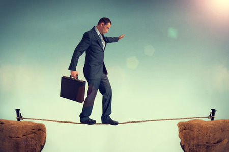 crevasse: businessman in a predicament balancing on a tightrope  Stock Photo