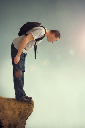 man looking down: man looking down from a rocky ledge with backpack
