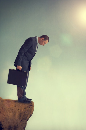 business dilemma: businessman facing a dilemma on a cliff edge