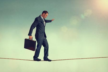hombre preocupado: empresario valiente mantener el equilibrio sobre una cuerda floja o highwire Foto de archivo
