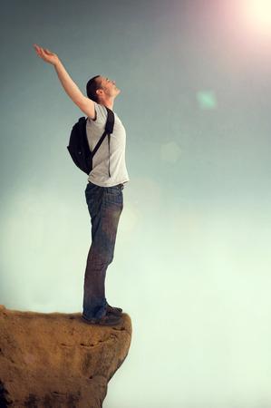 joyous man arms aloft giving praise on a rocky outcrop Stock Photo