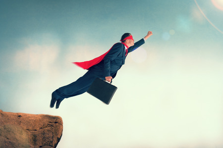 superhero businessman taking flight from a cliff ledge