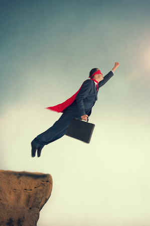 taking a risk: superhero businessman taking flight from a cliff ledge