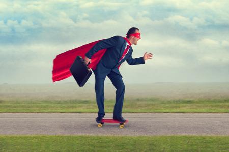 superhero businessman riding a skateboard making progress Foto de archivo