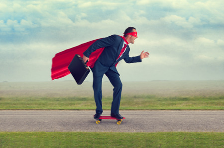 headway: superhero businessman riding a skateboard making progress Stock Photo