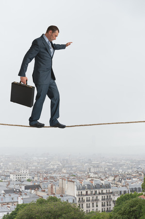 businessman walking across a tightrope above a city photo