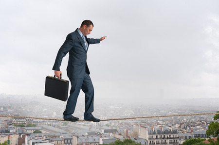 predicament: businessman walking across a tightrope above the city