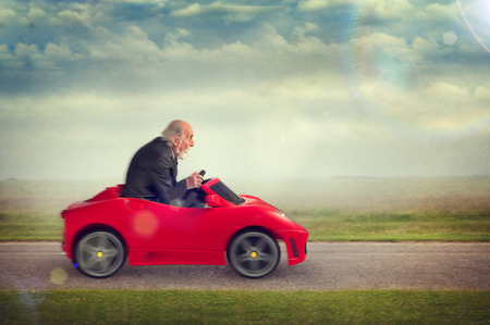 funny elderly: senior man enjoying driving a toy racing car