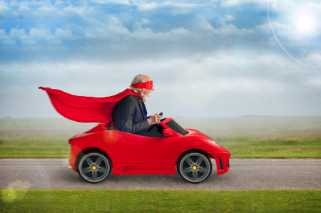 senior superhero with mask and cape driving a toy sports car Archivio Fotografico