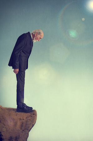 cliff edge: senior man standing alone on a cliff ledge