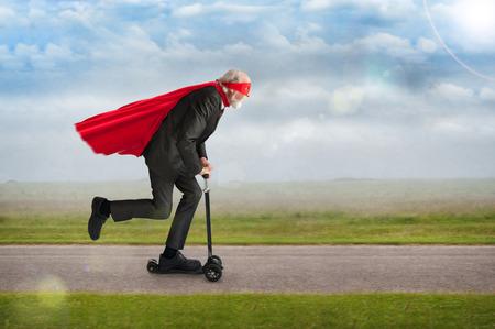 senior superhero man riding a scooter