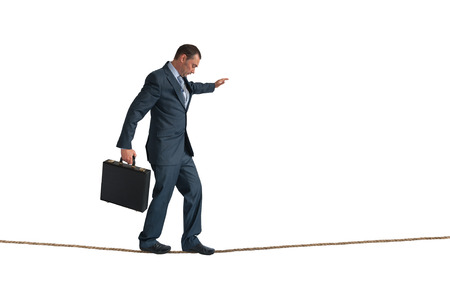 businessman balancing on a tightrope isolated on white Foto de archivo