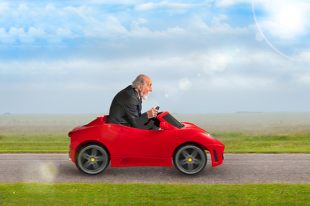 senior man in a suit driving a toy racing car  Standard-Bild