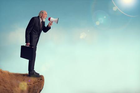 loudhailer: senior businessman yelling through a loudhailer from a cliff edge