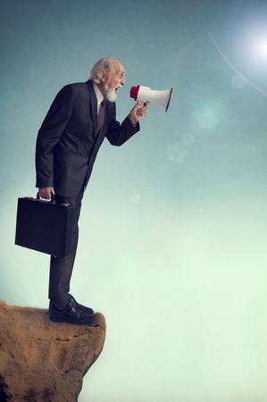loudhailer: Hombre de negocios mayor que grita meg�fono borde del acantilado