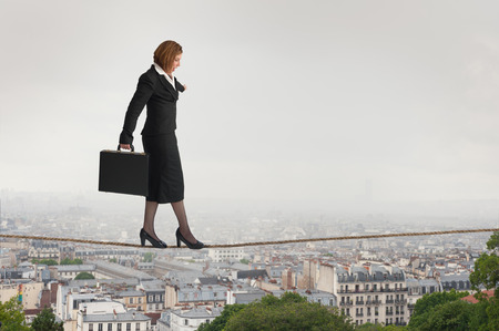 businesswoman walking a tightrope over city rooftops