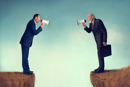 businessmen shouting through megaphones business conflict concept photo
