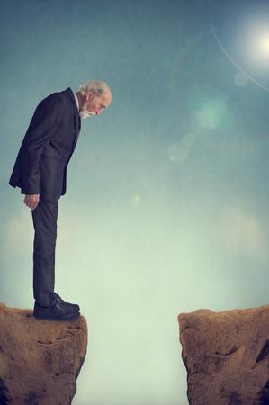 senior man looking down a mountain crevasse