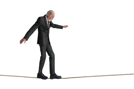 senior man walking a tightrope isolated on white Foto de archivo