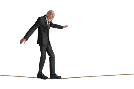 predicament: senior man walking a tightrope isolated on white Stock Photo