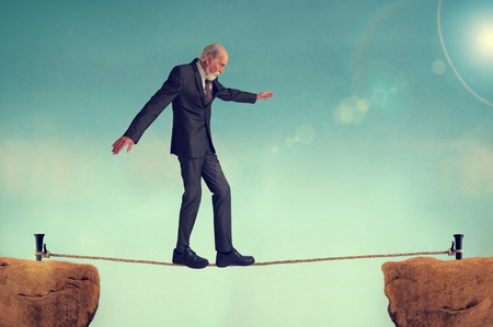 predicament: senior man walking on a tightrope or highwire