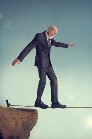 brink: senior man walking on a tightrope or highwire
