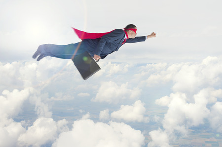 exceeding: superhero businessman flying above the clouds