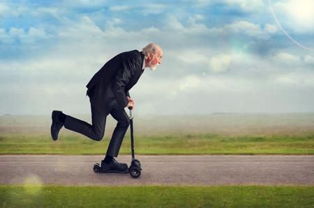personas en la calle: hombre mayor que monta una vespa activo y en�rgico Foto de archivo
