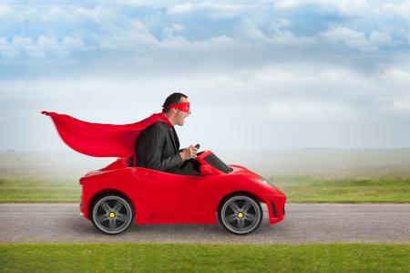 excitación: hombre superhéroe conducir un coche de carreras de juguete de color rojo a la velocidad