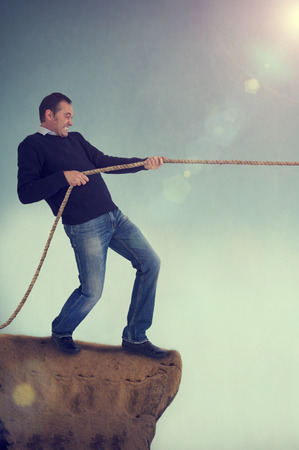 man pulling rope tug of war on a cliff edge adversity concept  photo
